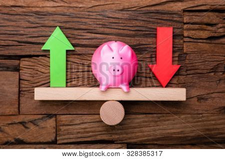 Up And Down Arrows And Piggybank On Seesaw On Wooden Desk
