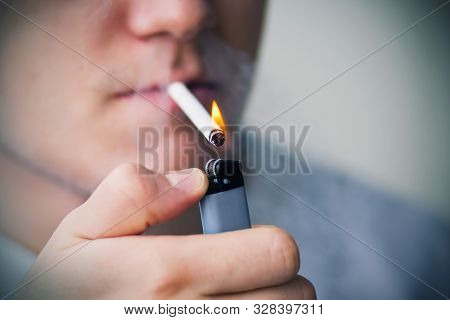 A Young Man Holds A Cigarette In His Mouth And Ignites It With A Gas Lighter. The Cigarette Smoulder