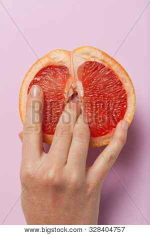 Two Female Fingers In Grapefruit, Woman Masturbation And Sex Concept. Vagina And Clitoris Symbol.
