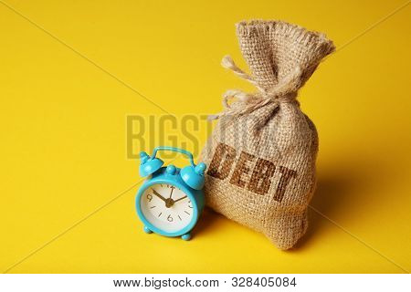 Taxes And Interest On Debt Payments. Overdue Payments, Penalties. Bag With Money And Clock On Yellow
