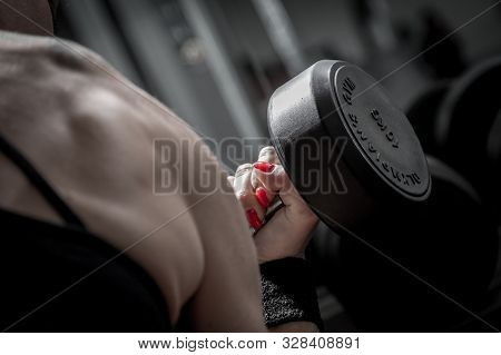 Close up on a female bodybuilder deltoid and trapeze, female bodybuilder doing exercises with dumbbell. poster