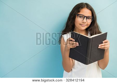 Portrait Of Preadolescent Girl Holding Book While Standing Against Plain Background