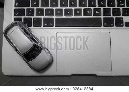 Car Model And Notebook On Grey Desk. About Car Business Concept Such As Transportation, Rental, Sell