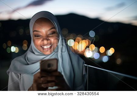 Young Muslim woman wearing scarf veil on urban city  street at night texting on smartphone with bokeh city light in background