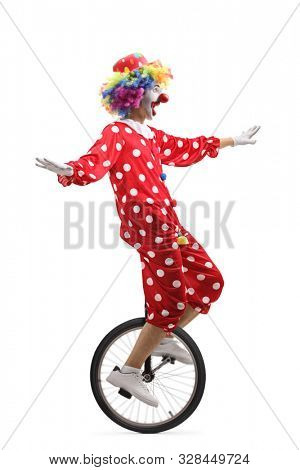 Full length profile shot of a cheerful clown riding a unicycle and making a funny grimace isolated on white background