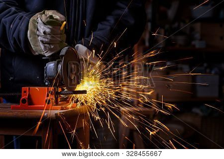 Hands Of A Craftsman With Working Gloves Cutting An Iron Bar With The Electric Angle Grinder Which S