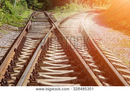 Bifurcation In The Railway Tracks. Rusty Railway Rails And Rotten Wooden Sleepers Are Overgrown With
