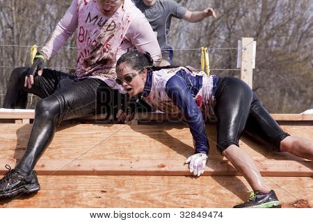 POCONO MANOR, PA - APR 28: A woman emerges from a tank filled with water and ice at Tough Mudder on April 28, 2012 in Pocono Manor, PA. The course is designed by British Special Forces.