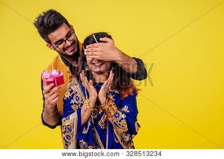 Beautiful Indian Woman In Traditional Sari And Happy Hindu Male Getting Together Gift Box In Yellow