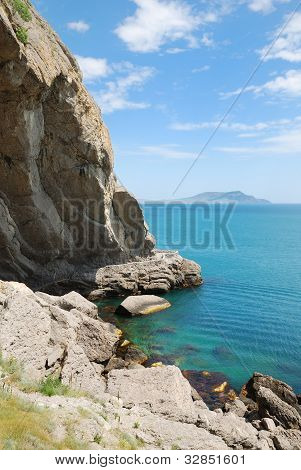 Grotto At The Foot Of The Mountain In The Calm Sea.