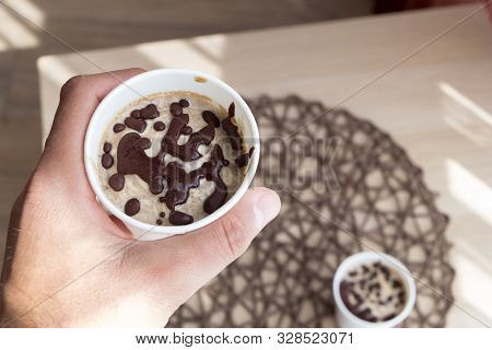 Male Hand Take A Cup With Raw Vegan Chocolate Ice Cream, Made From Bananas, Chocolate And Coconut Cr