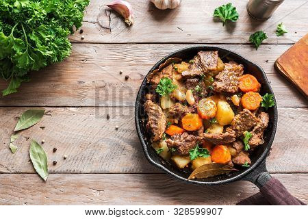 Beef Meat Stewed With Potatoes, Carrots And Spices On Wooden Background, Top View, Copy Space. Homem