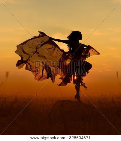 Beautiful Dancer Woman With Flying Dress And Veil At Sunst, Orange Background.