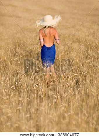 Beautiful And Sexy Woman In Straw Hat And Blue Dress From Behind Under Summer Sunshine At The Middle