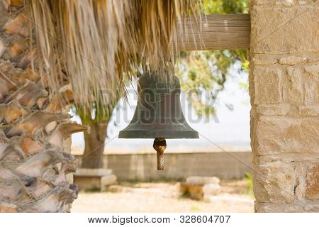 Ritual Sacral Bell Outdoor In Garden Of A Church, Next To A Palm Tree.
