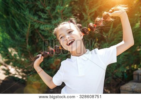 Happy Cute Small Girl Wearing White Shirt Having Fun Holding Her Braids In A Sunny Summer Park. Pine