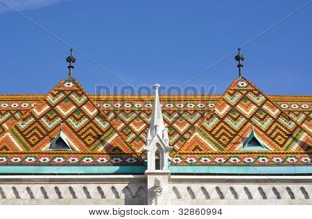 spire, garrets and roof of Matthias church clad with the typical ceramics Zsolnay tiles in Budapest