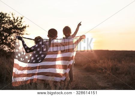 Happy Family, Dad And Daughter Holding The American Flag At Sunset. Dressed In White. The Concept Of