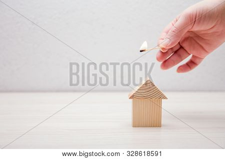 Hand Holds A Burning Match Over A Wooden Toy Dm On A White Background, Concept Of Security And Real