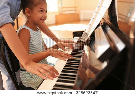 Young Woman Teaching Little Girl To Play Piano Indoors