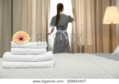 Stack Of Clean Towels With Flower On Bed And Blurred Chambermaid In Hotel Room, Closeup. Space For T
