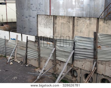 A Shabby Unsafe Fence Propped Up With Pieces Of Wood And Corrugated Iron Surrounding A Steel Industr