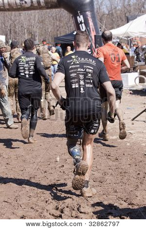POCONO MANOR, PA - APR 28: Participants run to cross the finish line at the Tough Mudder event on April 28, 2012 in Pocono Manor, Pennsylvania. The course is designed by British Royal troops.