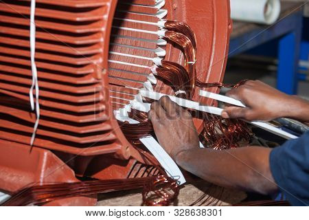African man rewinding a giant electric motor