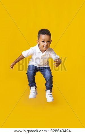 Adorable Afro Baby Boy Jumping Over Yellow Studio Background With Copy Space