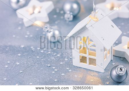 New Year Festive Background With Christmas Tree Garlands, Balls And Decorative Wooden Toy House