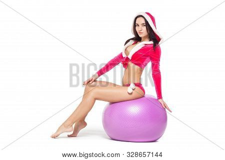 Christmas. Sports Fitness Girl In Red Sexy Santa Claus Costume Sits On A Fitness Ball. Isolated On W