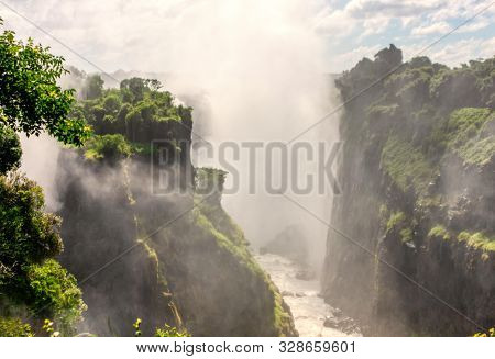 Victoria falls is the largest fall on the African continent at the border of Zimbabwe, Zambia and Botswana, misty fall at the sunset