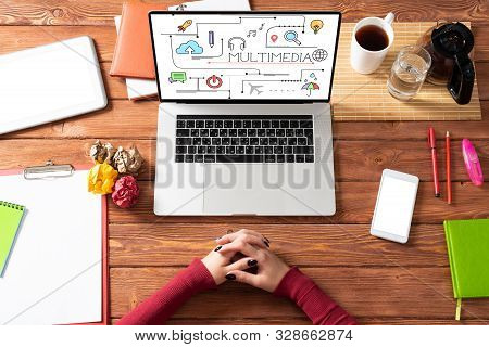 Multimedia Education Concept With Office Workspace. Flat Lay Wooden Desk With Laptop, Woman Hands An