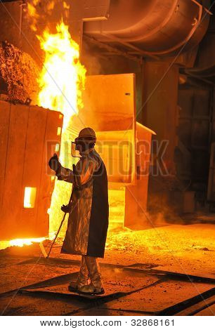A Steel Worker Takes A Sample From Oven