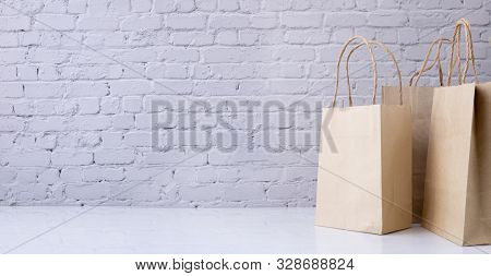 Kraft Paper Shopping Bags With Copy Space On Brick Wall Texture Background.