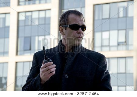 A Stern Man In A Black Coat With A Radio On The Background Of The Business Center, The Head Of The P