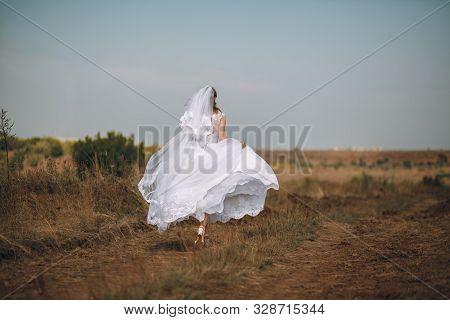 Romantic Beautiful Bride. Woman In A Wedding Dress Runs Across The Field. The Bride In A Beautiful W