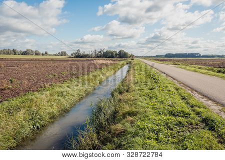 Dutch Polder Landscape With A Ditch And Country Road On A Cloudy Day In The Fall Season. The Lines A