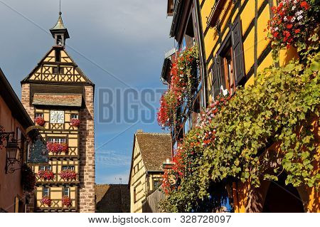 Riquewihr, France, October 13, 2019 : Tower Of The Town And Flowered Balcony. Popular Tourist Attrac
