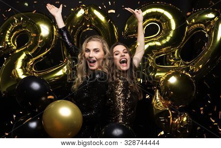 Happy Gorgeous Girls In Stylish Sexy Party Dresses Holding Gold 2020 Balloons, Having Fun At New Yea