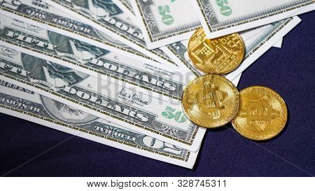 Bitcoins On The Background Of Dollars. Golden Bitcoins. New Virtual Money. Symbolic Coins Of Bitcoin