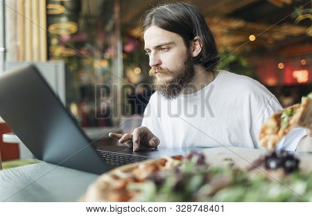 Hot Delicious Pizza Is Waiting For A Youngster Working Keen By A Laptop