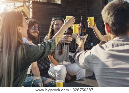Jolly Friends Drinking Beer During Friday Evening Party On A Loft Balcony