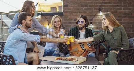 Youngsters spend spare time on a loft terrace with beer, pizza and guitar poster