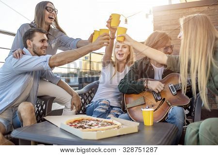 Partying Youngsters Raising Their Glasses To Honour Their Friend, Who Plays And Sings For Them