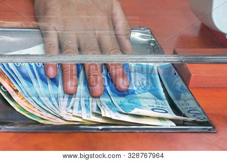 Cash Money Israeli Shekel, At Bank Office Or Currency Exchanger. Male Hand With Shekel Money In Cash
