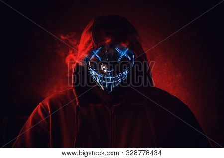 Man In Angry And Scary Lighting Neon Glow Mask In Hood On Dark Red Background. Halloween And Horror