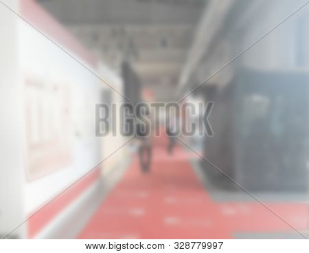 Defocused Background Of A Trade Show With People Visiting The Commercial Exhibition. Intentionally B