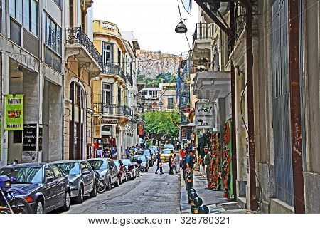 Athens, Attica, Greece - October 17, 2018:  Tourists Walking And Shopping Along A Motorcycle And Car