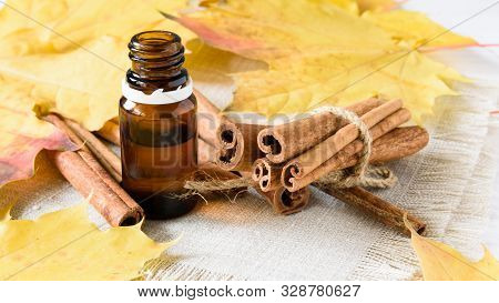 Close-up, Cinnamon Sticks And Cinnamon Oil On A White Wooden Background